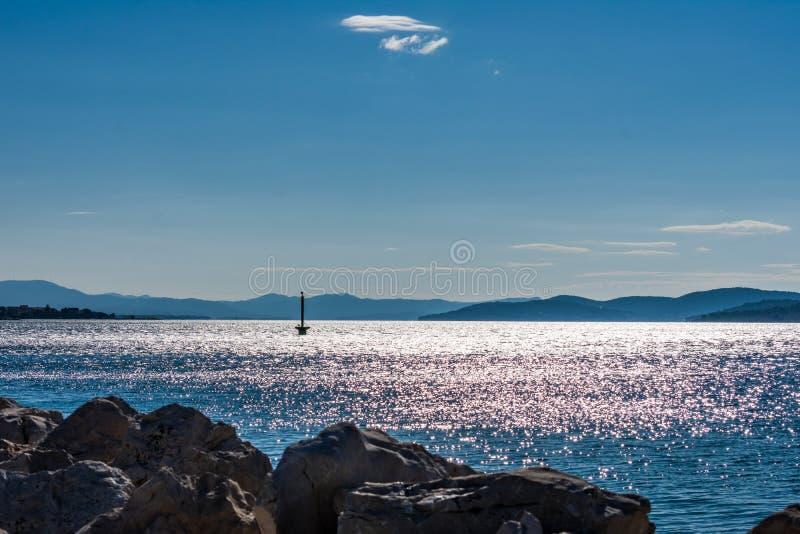 Vista di un faro nel mare adriatico con una vista delle isole durante l'alba, Dalmazia in Croazia immagini stock libere da diritti