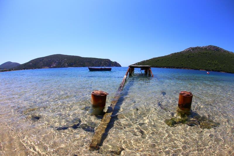 Vista di un pilastro di legno rovinato e un vecchio peschereccio e montagne nei precedenti del sithonia Grecia Fisheye fotografie stock libere da diritti