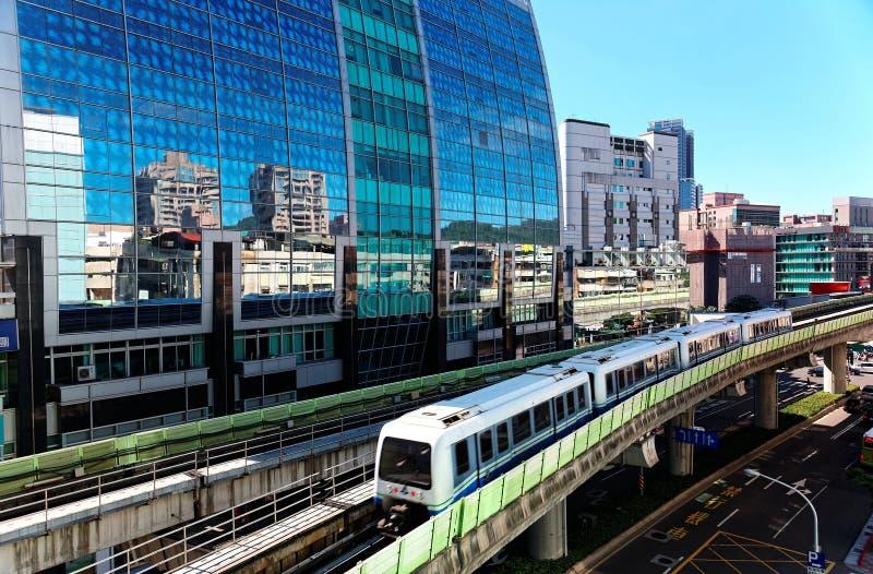 Vista di un treno che viaggia sulle rotaie elevate del sistema della metropolitana di Taipei da una costruzione moderna delle par immagine stock
