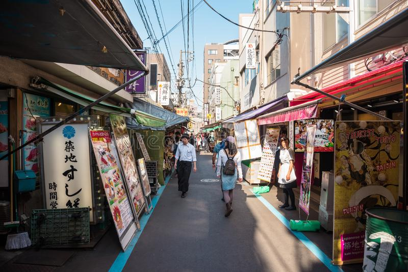 Vista di un vicolo stretto allineato con i negozi ed i ristoranti nel mercato esterno di Tsukji a Tokyo centrale fotografia stock libera da diritti