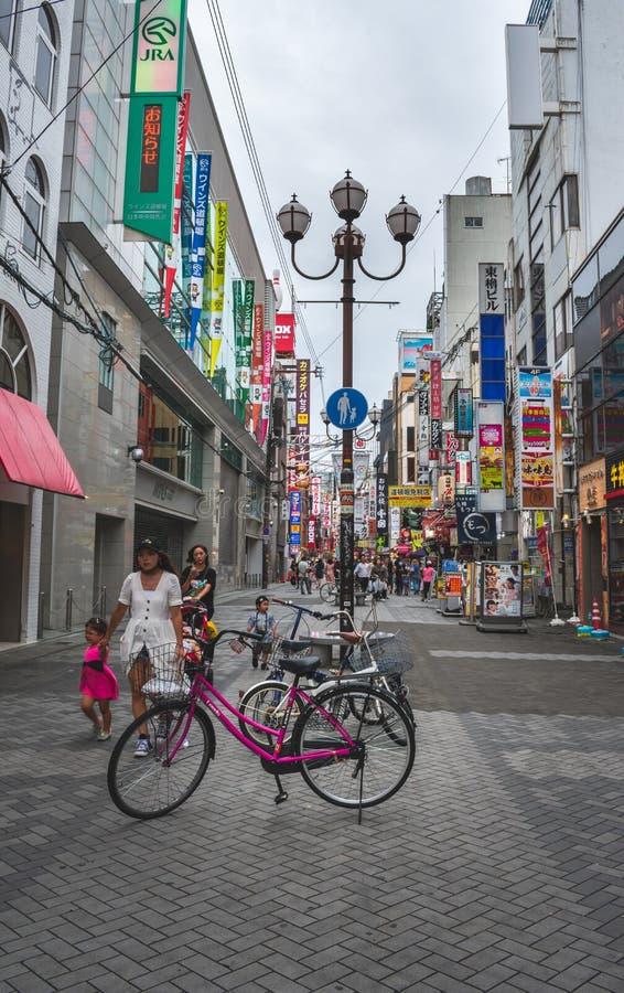 Vista di una bicicletta rosa davanti alla zona commerciale vivace ed occupata di Osaka nel Giappone immagine stock libera da diritti