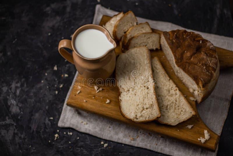 Vista di una brocca di latte e di recente di pane bianco al forno casalingo su un fondo nero immagini stock libere da diritti