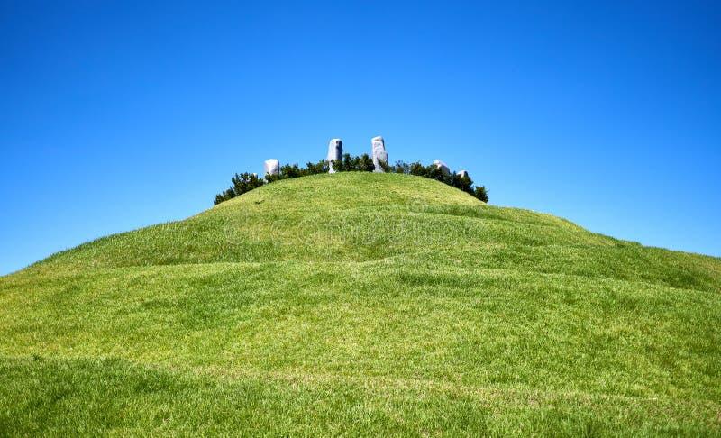 Vista di una collina verde con pietre appoggiate in alto fotografia stock
