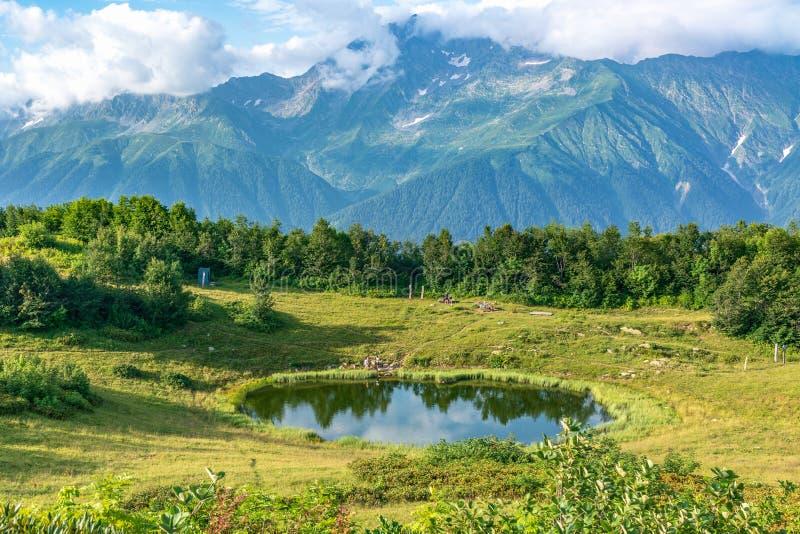 Vista di una radura della montagna con un lago trasparente dello specchio e turisti, circondati da erba ed alberi e alte montagne fotografie stock