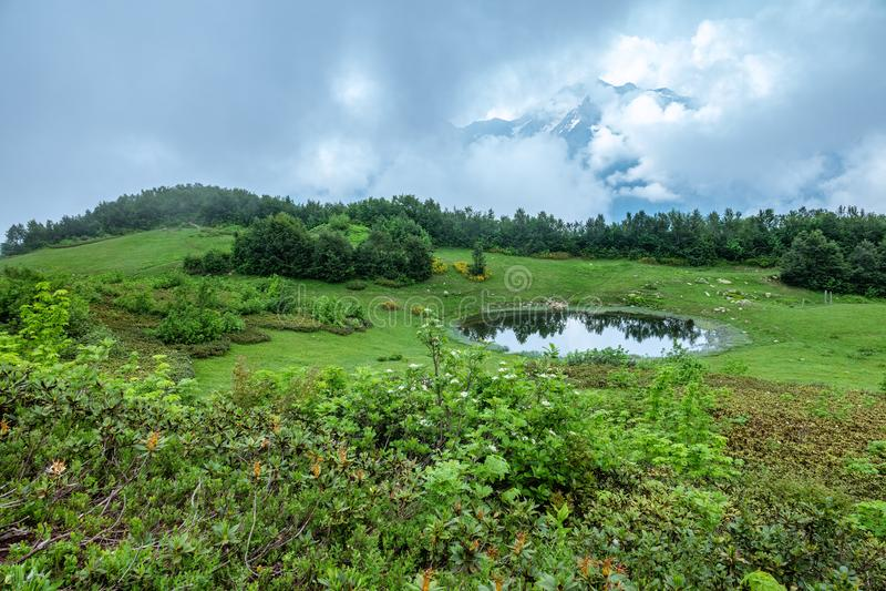 Vista di una radura della montagna con un lago trasparente e le alte montagne dello specchio con i picchi innevati nella distanza fotografie stock