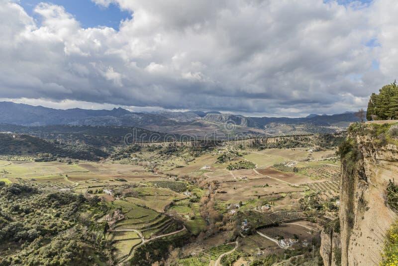 Vista di una valle con le aree del pascolo e di orticolo circondata dalle montagne vedute dalla città Ronda fotografia stock libera da diritti