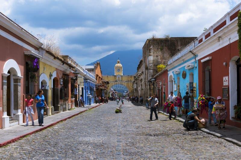Vista di una via del ciottolo nella vecchia città dell'Antigua con il vulcano del Agua sui precedenti, nel Guatemala fotografia stock libera da diritti
