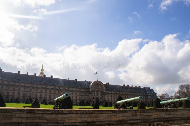 Vista di vecchi cannoni bronzei sui precedenti del palazzo e sul cielo blu con le nuvole immagini stock libere da diritti