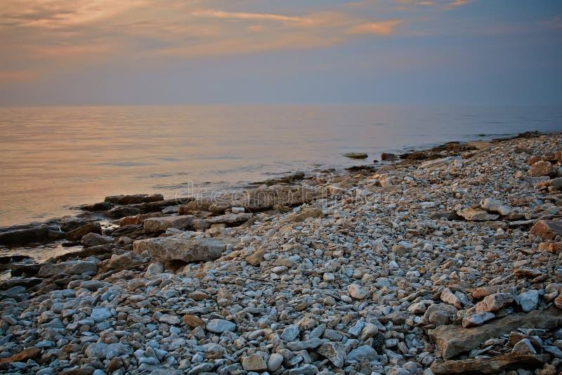 Vista di vista sul mare Spiaggia rocciosa nella sera Riva del ciottolo Foto tinta fotografia stock
