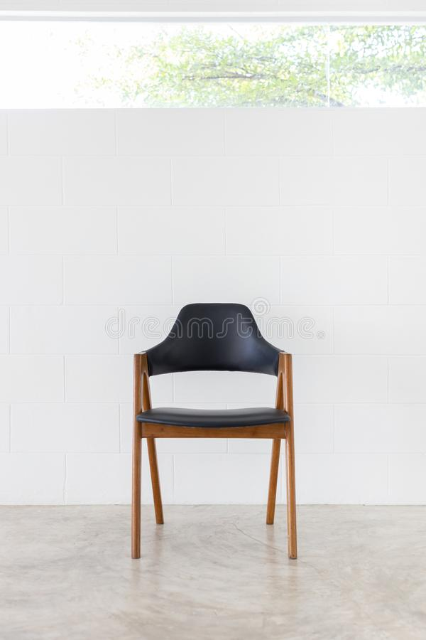 Vista dianteira da ?nica cadeira de couro de madeira no fundo branco do muro de cimento e da janela fotografia de stock royalty free