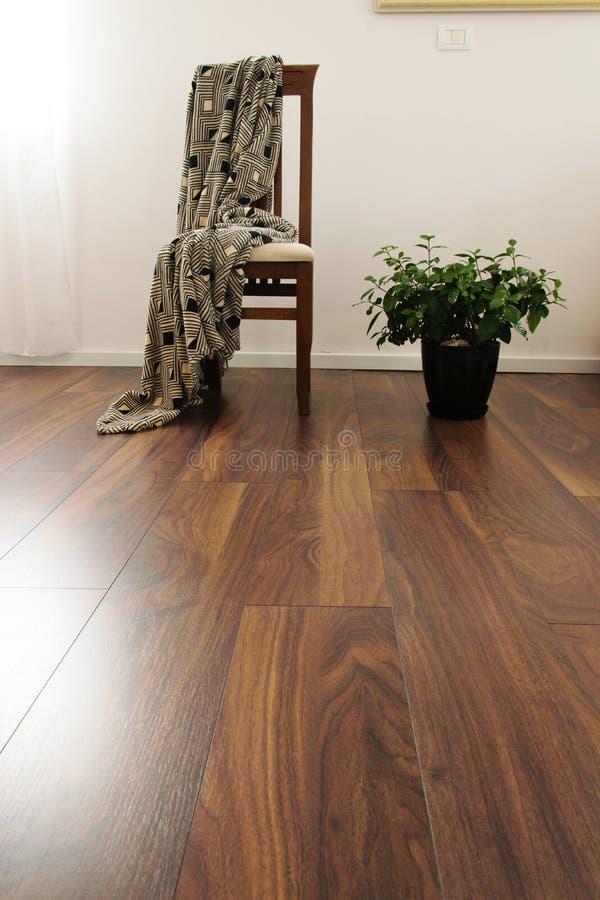 Vista dianteira da cadeira de madeira, da manta e da planta em pasta da gardênia na sala de visitas decoração do design de interi foto de stock royalty free