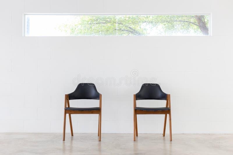 Vista dianteira da cadeira dois de couro de madeira no fundo branco do muro de cimento e da janela fotos de stock