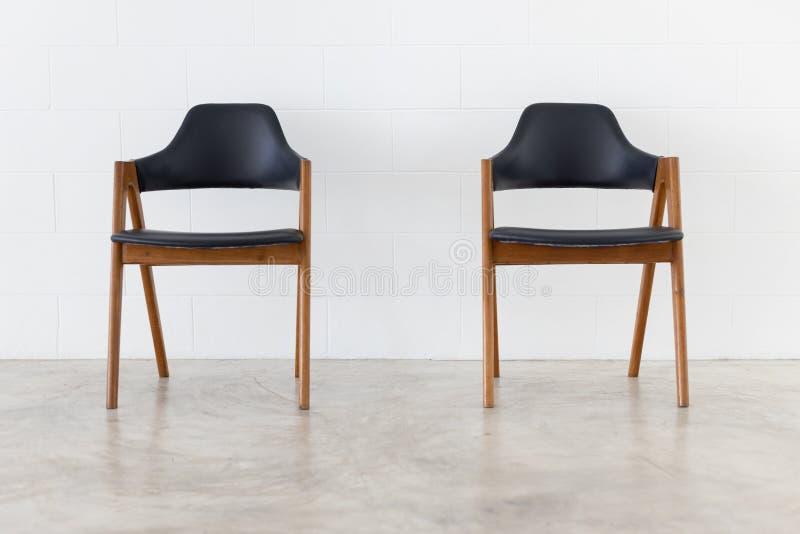 Vista dianteira da cadeira dois de couro de madeira no fundo branco do muro de cimento imagens de stock