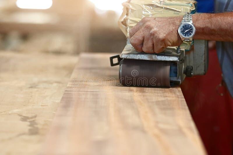 Vista dianteira da máquina de lixar da correia que trabalha em uma madeira da parte com mãos do trabalhador com espaço da cópia F fotos de stock royalty free