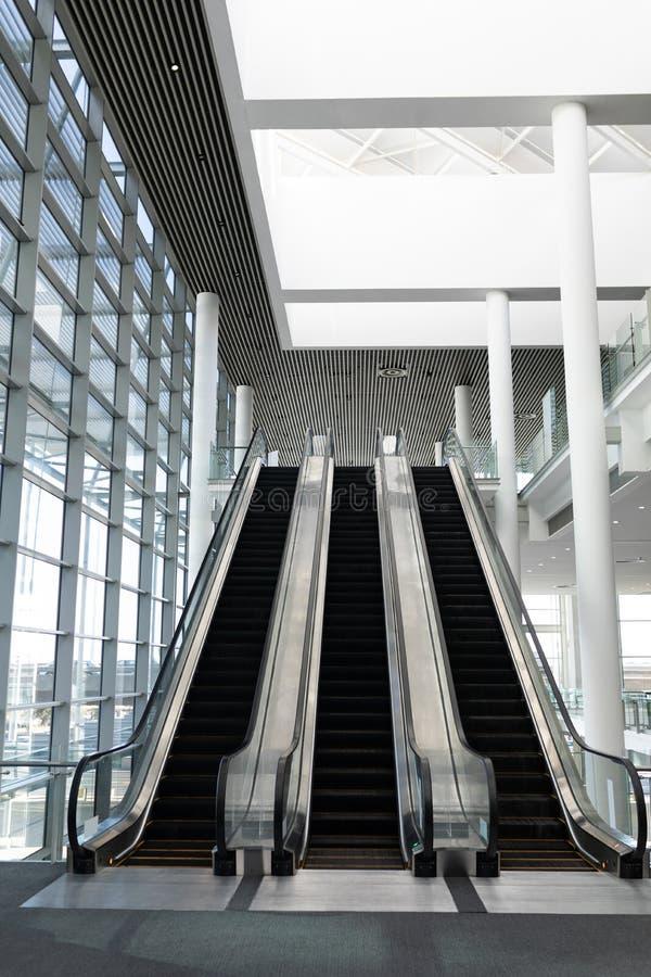 Vista dianteira de três escadas rolantes modernas em uma entrada do escritório imagens de stock royalty free