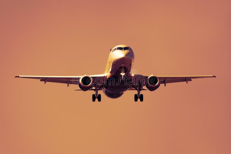 Vista dianteira de um avião contra um céu alaranjado foto de stock