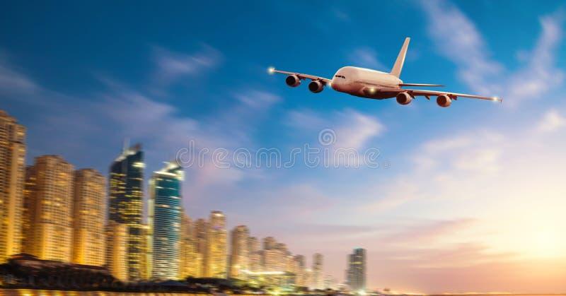 A vista dianteira do avião comercial, borra a cidade moderna no fundo imagens de stock