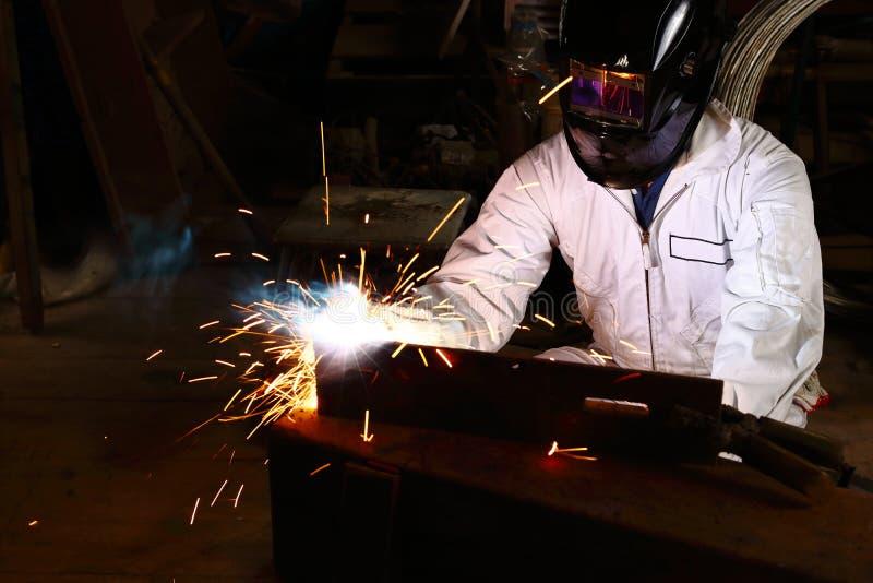 Vista dianteira do soldador profissional no uniforme branco com aço protetor da soldadura do capacete com a faísca na oficina Tra foto de stock royalty free