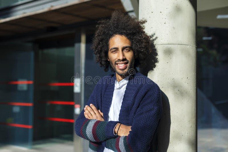 A vista dianteira dos braços afro de sorriso de um homem cruzou-se ao olhar o ar livre da posição da câmera no dia ensolarado fotos de stock