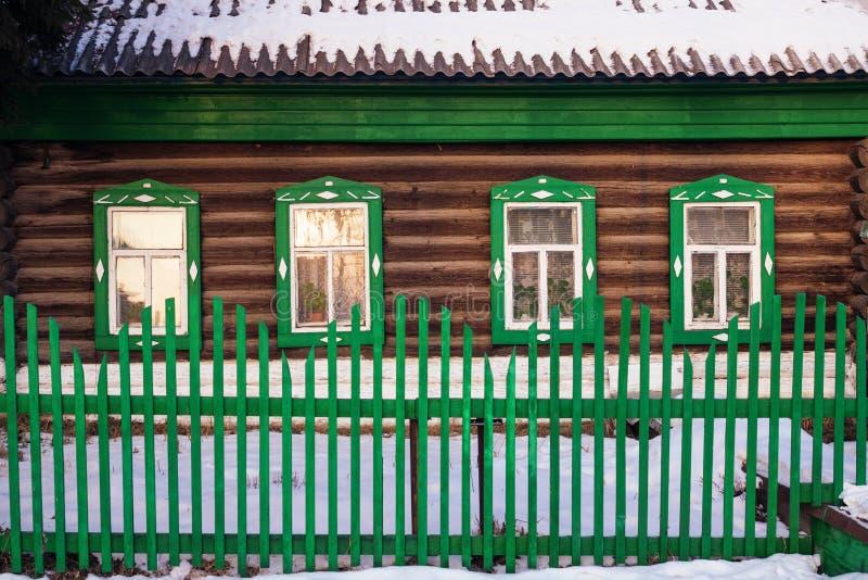 Vista dianteira na fachada verde da cabana rústica de madeira no inverno fotos de stock royalty free