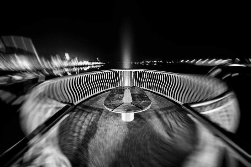 Vista din?mica de uma ponte iluminada da arquitetura sobre um rio durante a noite imagens de stock royalty free