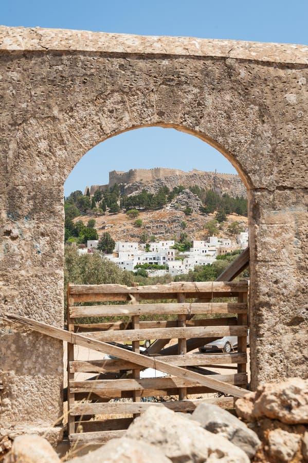 Vista distante com a abertura de pedra do arco na cidade e no castelo de Lindos com ruínas antigas da acrópole no dia morno ensol fotos de stock