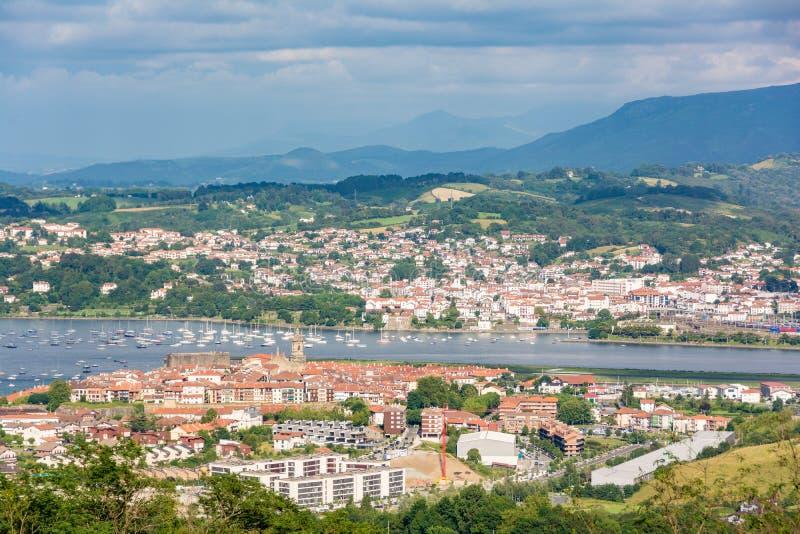 Vista distante das vilas dos pescadores da beira de Hondarribia e de Hendaya no país Basque, Espanha imagem de stock