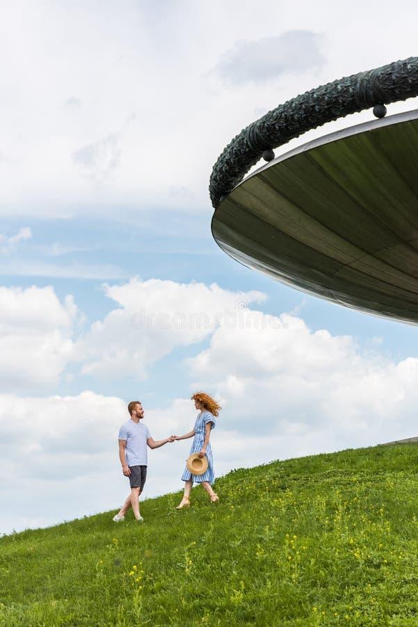 vista distante de los pares del pelirrojo que llevan a cabo las manos en la colina herbosa cerca del edificio contra azul imagen de archivo libre de regalías