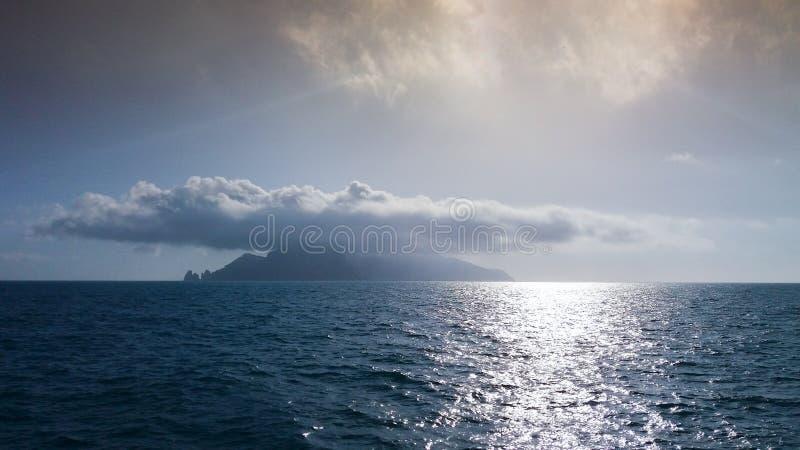 Vista distante de una isla debajo de una nube grande fotos de archivo libres de regalías