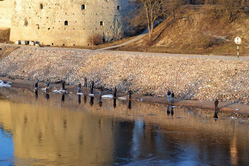 Vista distante dos pescadores no banco de rio ao longo da parede antiga da fortaleza e da torre no dia de mola imagem de stock royalty free