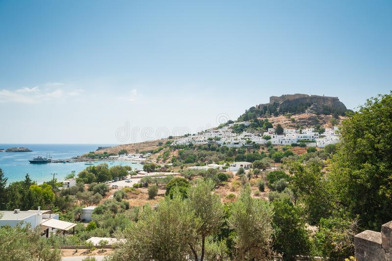 Vista distante na cidade e no castelo de Lindos com ruínas antigas da acrópole no dia morno ensolarado Console do Rodes, Greece e fotos de stock royalty free