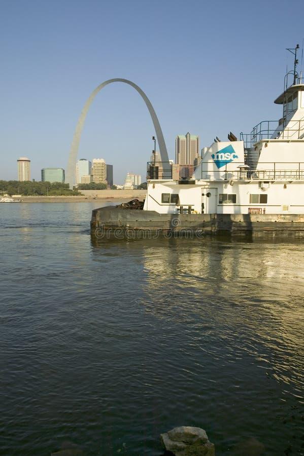 Vista diurna del barco del tirón que empuja el río Misisipi de la gabarra hacia abajo delante del arco de la entrada y el horizon foto de archivo