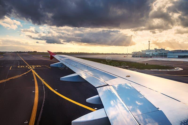 A vista do aeroporto e o avião voam do interior O plano está pronto à partida na pista de decolagem imagem de stock