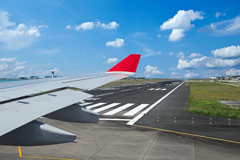 Vista do avião com a asa na pista de decolagem do aeroporto pronta para a decolagem no céu nebuloso azul dianteiro fotos de stock