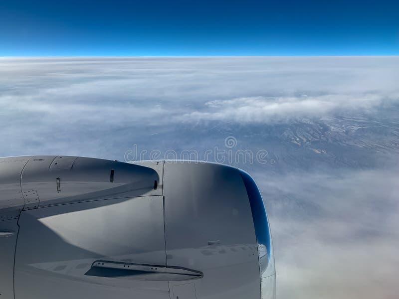 Vista do avião da imagem refletindo da asa do plano, e das montanhas através das nuvens fotografia de stock