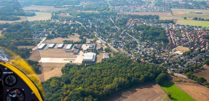 Vista do avião ultraleve a um subúrbio alemão com campos a pouca distância do mar, prados, uma floresta e uma área industrial imagens de stock
