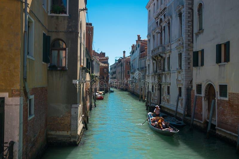 Vista do barco venetian tradicional da gôndola no canal da água com pares de amantes que tomam um passeio romântico e relaxando d fotos de stock royalty free