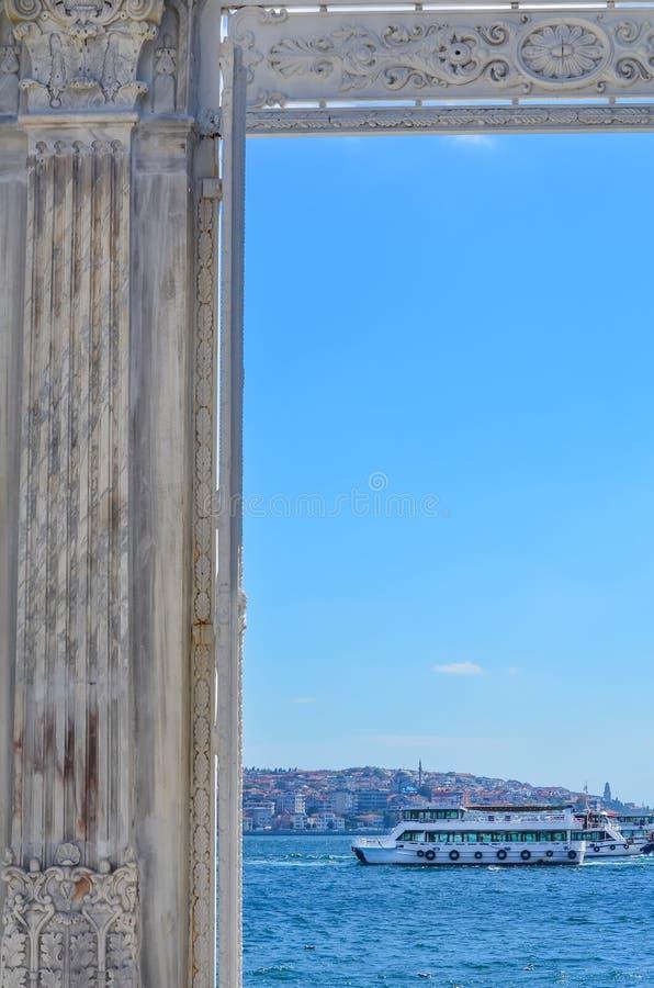 Vista do Bosphorus e do barco branco através da porta do palácio de Dolmabahche Istambul, Turquia fotografia de stock royalty free