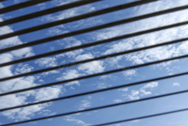 Vista do céu azul através da grelha fotos de stock