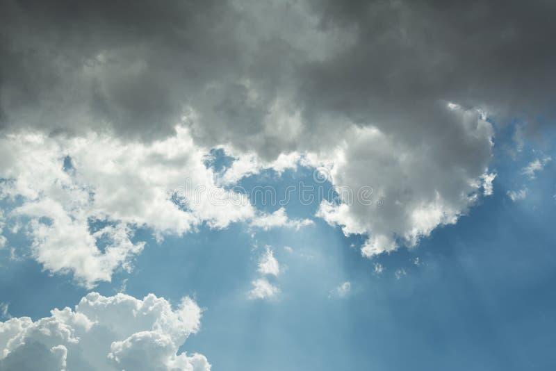Vista do céu da cor azul e nuvens cinzentas com que os raios do sol fazem sua maneira fotos de stock royalty free