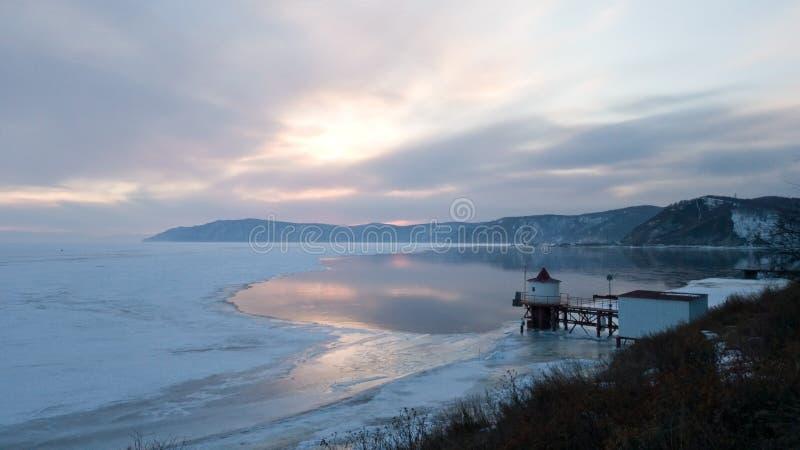 Vista do cais perto da vila Listvyanka A fonte do rio de Angara do Lago Baikal Inverno em Sibéria Por do sol imagens de stock royalty free