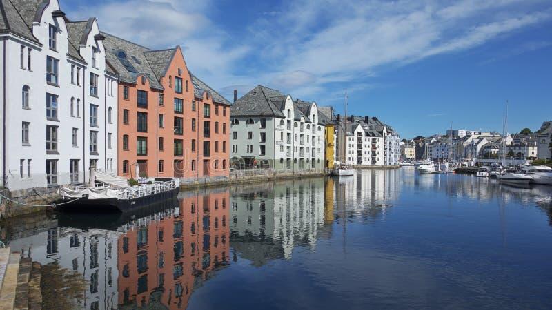 A vista do canal azul claro famoso alinhou com as construções de Art Nouveau em Alesund, Noruega foto de stock