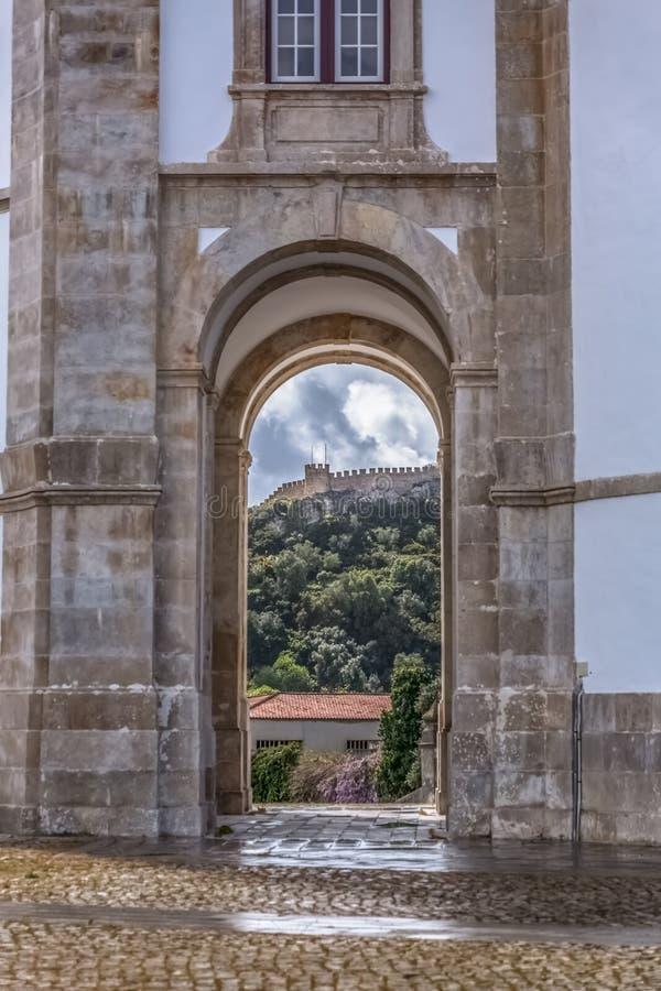 Vista do castelo e da fortaleza dos obidos, entre colunas dos arcos de Lord Jesus do santuário de pedra foto de stock royalty free