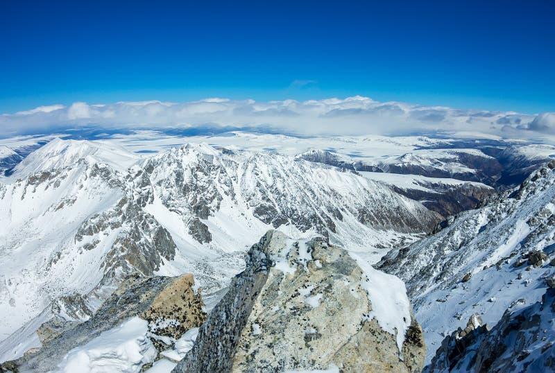 Vista do cume à parte superior das montanhas nevados ao vale e ao horizonte foto de stock