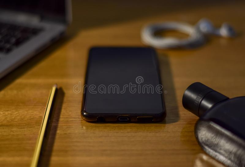 Vista do desktop de madeira com smartphone, portátil, fones de ouvido, lápis e perfume imagem de stock royalty free