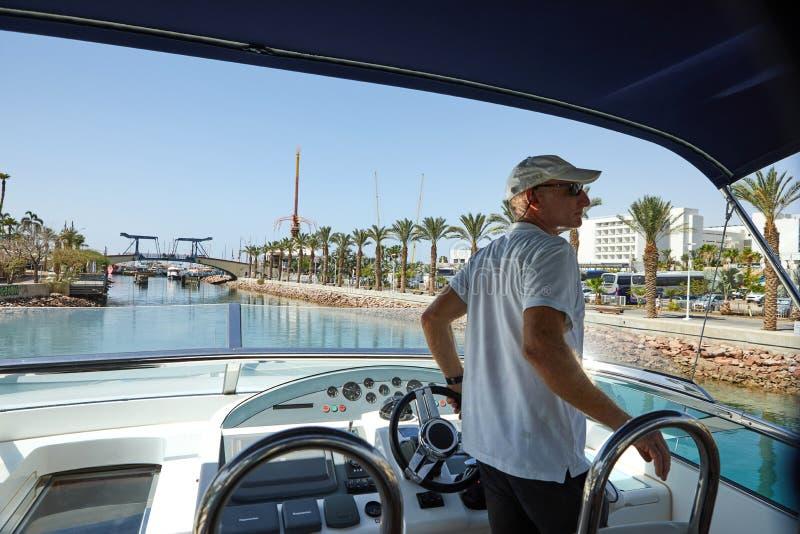 Vista do golfo de Eilat com iate luxuosos Capitão que está na ponte do controle que espera a abertura da ponte fotos de stock royalty free