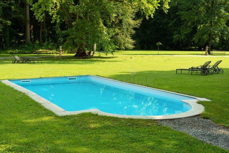 Vista do gramado, da piscina, das camas do sol e das árvores verdes bonitos foto de stock royalty free