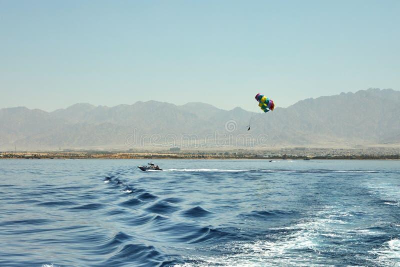 A vista do iate luxuoso ao Mar Vermelho aberto com o voo da atração em um paraquedas amarrado a um barco imagem de stock royalty free