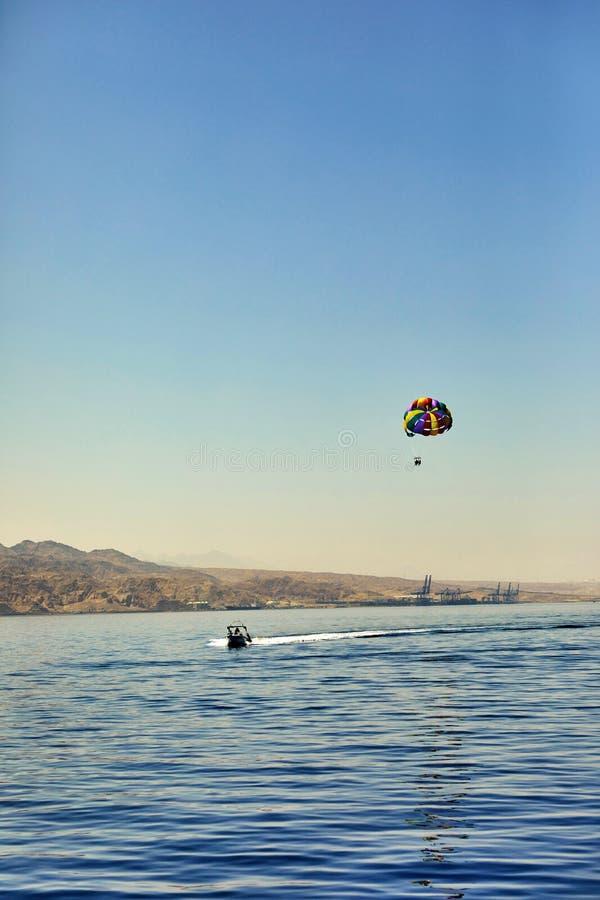 A vista do iate luxuoso ao Mar Vermelho aberto com o voo da atração em um paraquedas amarrado a um barco foto de stock
