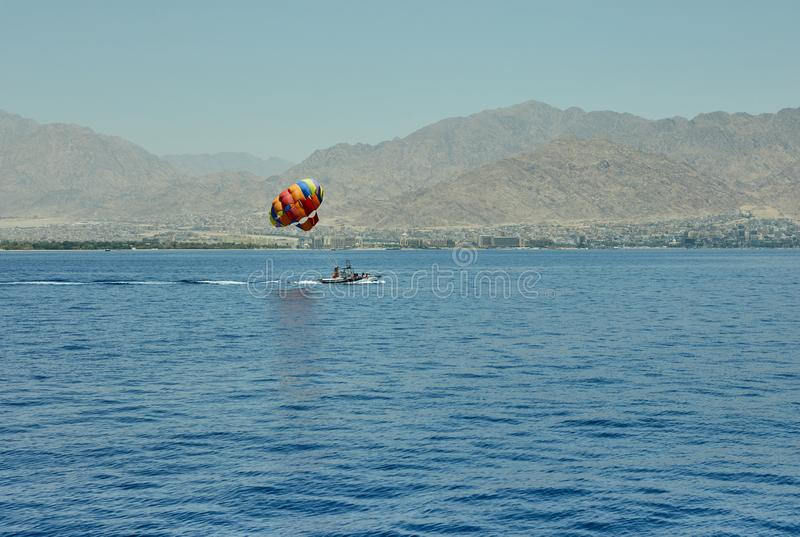 A vista do iate luxuoso ao Mar Vermelho aberto com o voo da atração em um paraquedas amarrado a um barco imagem de stock